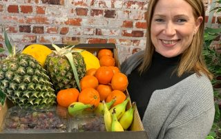 Yvonne Tweddle with a crate of Jupiter Group fresh fruit